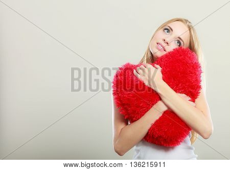 Valentines day love and relationships concept. Blonde long hair young woman hugging heart shaped pillow love symbol