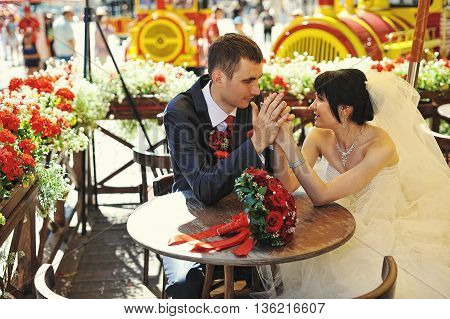 Happy wedding couple laughing on table at wedding