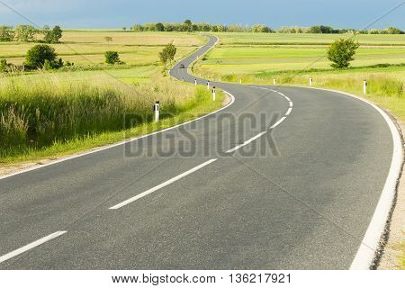 Empty country road winding through green meadow