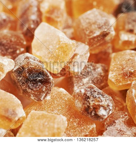 Surface coated with multiple large brown rock sugar crystals as a background composition