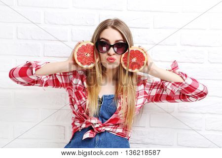 Portrait Of A Beautiful Hipster Girl With Grapefruit On A White Brick Wall Background