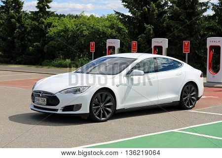 PAIMIO, FINLAND - JUNE 4, 2016: White Tesla Model S electric car leaves Tesla Supercharger station. Charging the battery from 10 to 80 percent takes about 40 minutes.