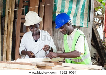 The teacher explains to his trainee how to take measurements of the wood.