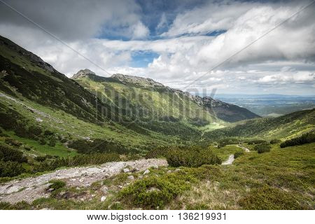 Europe, Poland, Polish high Tatras. The trail between two mountain range, cloudy sky, summer, green mountain forest
