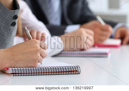 Close up view of students or businesspeople hands writing something during conference. Business meeting blogging or professional education concept
