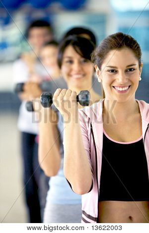 woman holding free weights at the gym
