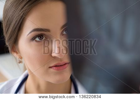 Young female medical doctor or intern looking at lungs x ray image standing at her office. Radiology healthcare medical service or education concept. Close up shot