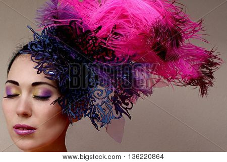 Close-up portrait of beautiful young woman in lace lilac purple hat fascinator with feathers on grey background. Fashion professional violet purple shades make-up. Model shot.