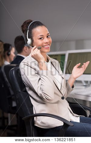 Young female consultant sitting on a chair and explaining something to the client by telephone