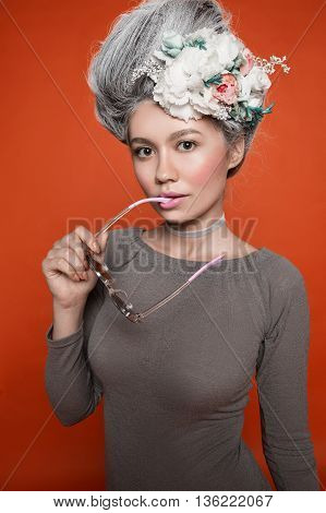 Beautiful girl with nude make up, natural browes, pink lips. White grey hair with diffrent flowers, sunglasses in her mouth
