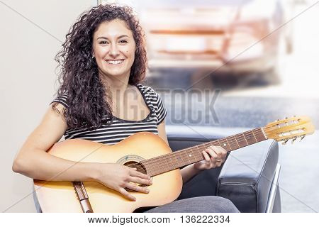 Young Female Guitarist Playing At Home On The Couch