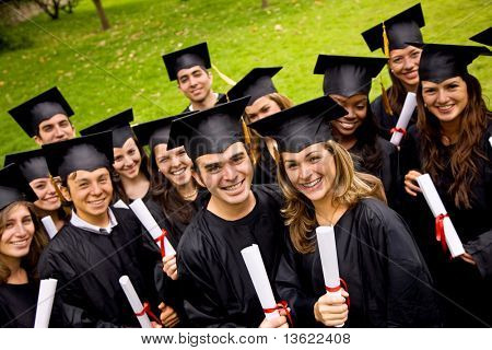 happy graduation students with diplomas outdoors