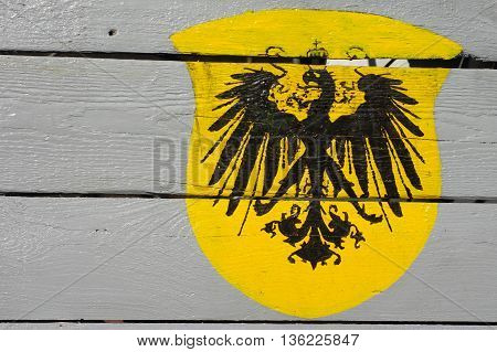Heraldic sign eagle black with a crown on a yellow field.