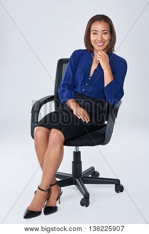 Successful business executive sits on office chair smiling, happy having job satisfaction