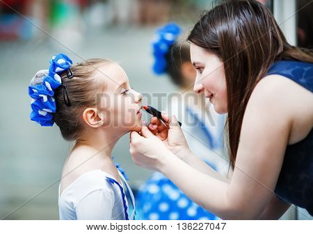 Mother putting lipstick on her daughter on mirror background. Mom helping little daughter to use lipstick before a dance performance. Mom makes make-up her daughter. Shallow depth of field. Selective focus.