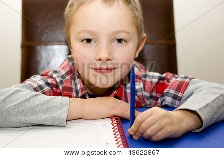Young Boy ready to start his School homework with pen and paper