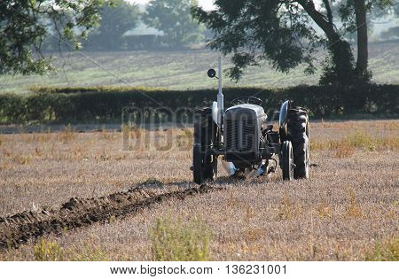 A Vintage Tractor Ploughing a Farmers Field.