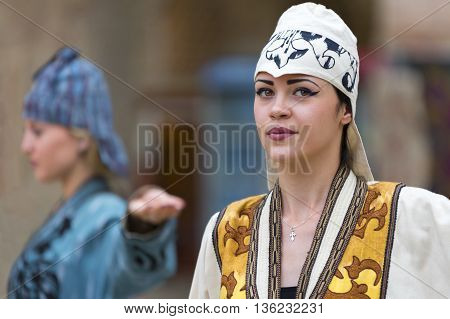 BUKHARA, UZBEKISTAN - MAY 20, 2016: Models in a fashion show of traditional hats and clothes of Uzbekistan.