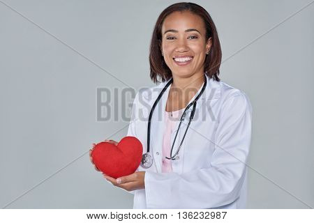 Happy smiling female doctor holding red heart isolated on grey background, heart smart healthy concept