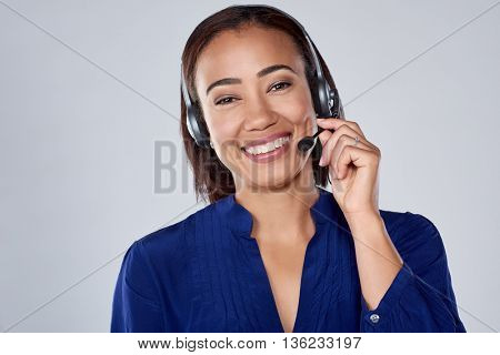 Pretty mixed race woman smiling with headset, isolated in studio
