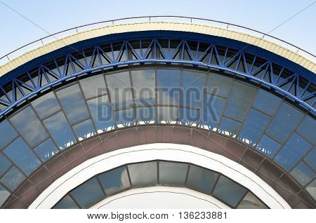 Detail of the facade a circular shape of a modern building. The design of the metal truss and wall with glass panels.