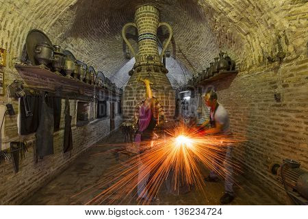 BUKHARA, UZBEKISTAN - MAY 21, 2016: Blacksmith hammers the iron and sparks fly, in Bukhara, Uzbekistan.