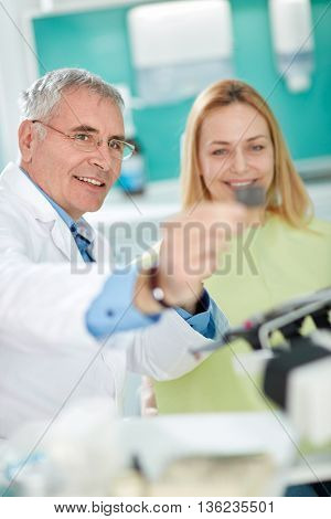 Male senior dentist with female patient look at dental snapshot