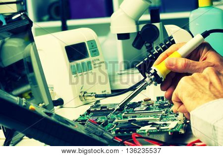 The soldering of chips on the printed circuit board. Toned photo