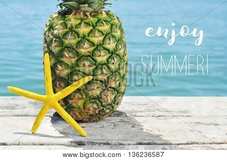 closeup of a yellow starfish and a pineapple on a weathered wooden pier with the ocean in the background and the text enjoy summer