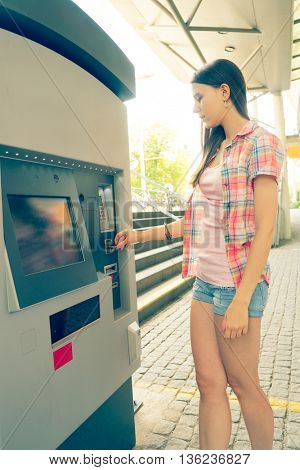 Young woman take cash in atm. Toned image