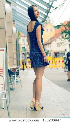 Pretty girl with long hair wearing a short dress in the city. Young woman turns back. Toned photo