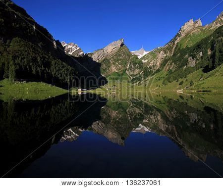 Summer morning in Appenzell Canton. Lake Seealpsee and mountains of the Alpstein Range.