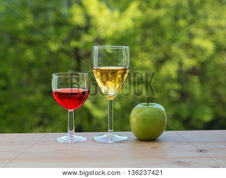 wine glasses and green apple on table in the garden