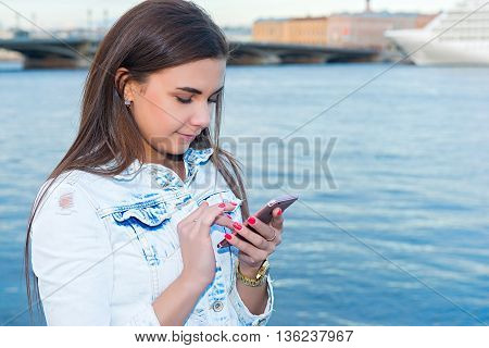 girl walking along the promenade and talking on the phone