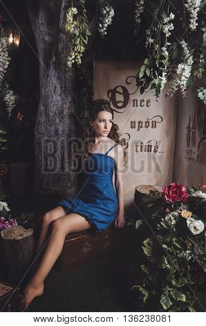 Studio portrait of romantic beautiful teen girl with long wavy hair blue dress sitting on retro suitcase surrounded blooming floral magic garden. Beauty female about princess walking mistery forest. Creative concept Once upon a time in fantasy stylization