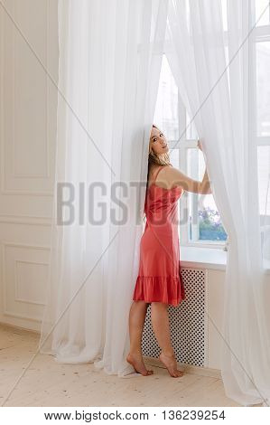 Early in the morning the woman sitting on the edge of the window thinking about the upcoming day