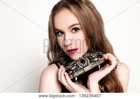 Portrait Of Beautiful Young Blonde Girl In Black Dress Holfing Her Handbag. Fashion Photo, Close Up