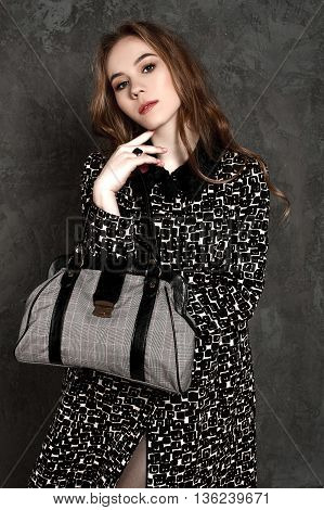 Fashion Girl With Handbag Posing At The Background Weariing A Coat
