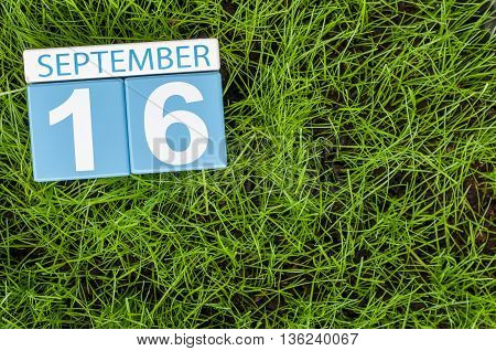 September 16th. Image of september 16 wooden color calendar on green grass lawn background. Autumn day. Empty space for text.