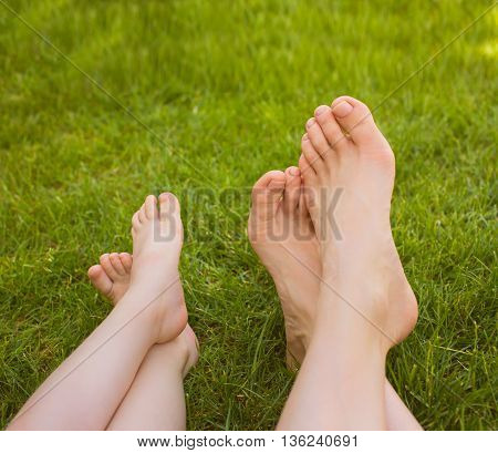 Close up female and child crossed legs lying on the grass in a park.