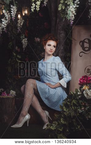 Portrait of romantic redhead young woman with wavy hairstyle, blue vintage dress, white elegant shoes, lace tights, sitting on retro suitcase surrounded blooming floral magic garden with street light. Beauty female walking mistery forest.