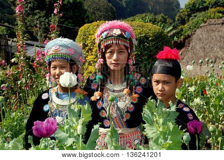 Doi Pui Thailand - December 24 2006: Thai family wearing vintage hilltop tribal village clothing in a garden of opium poppies