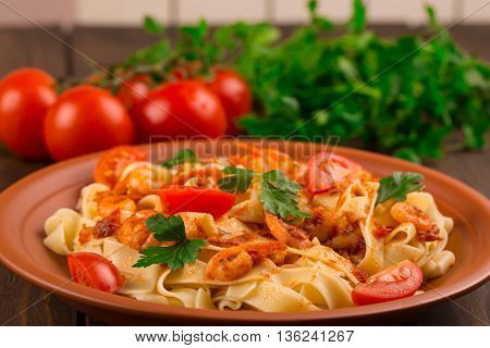 Fettuccine pasta with shrimp tomatoes and herbs. wooden background