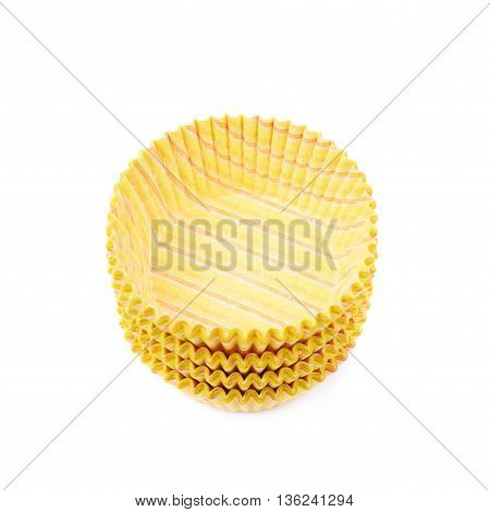 Pile of multiple yellow paper cupcake cups, composition isolated over the white background