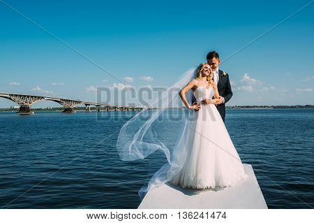 The Bride And Groom Take Pictures Near The River
