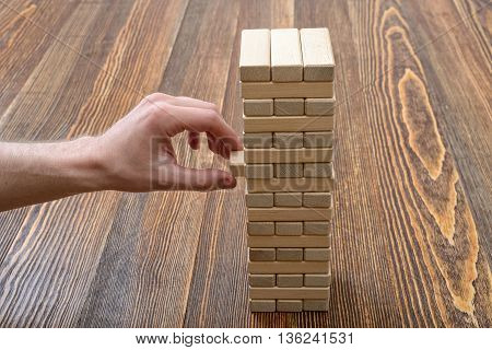Close-up hands of man pulls out wooden bricks. Removing blocks from a tower. Keeping balance. Full concentration. Entertainment activity. Game of physical and mental skill. Close-up photo.