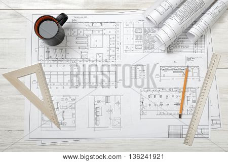 Rolls of drawing sketches, magnifier, ruler and protractor are on wooden surface. Top view compositin. Workplace of architect or constructor. Engineering work. Construction and architecture. Architect drawing. Exact calculation.