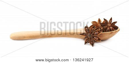 Chinese star anise seed served in a wooden spoon, composition isolated over the white background