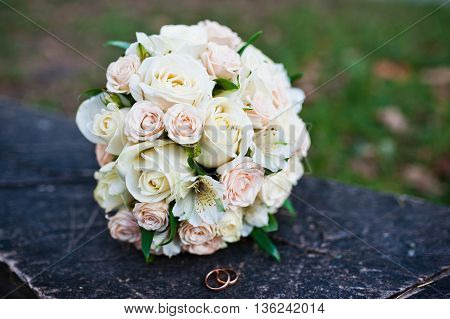 Wedding Bouquet Of Roses With Rings On Wooden Bench