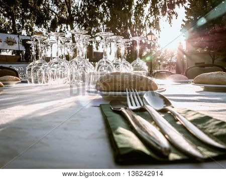 table with silverware and glasses ready for dinner at sunset
